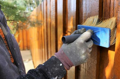 re-staining-weather-wooden-fence-with-big-stain-brush